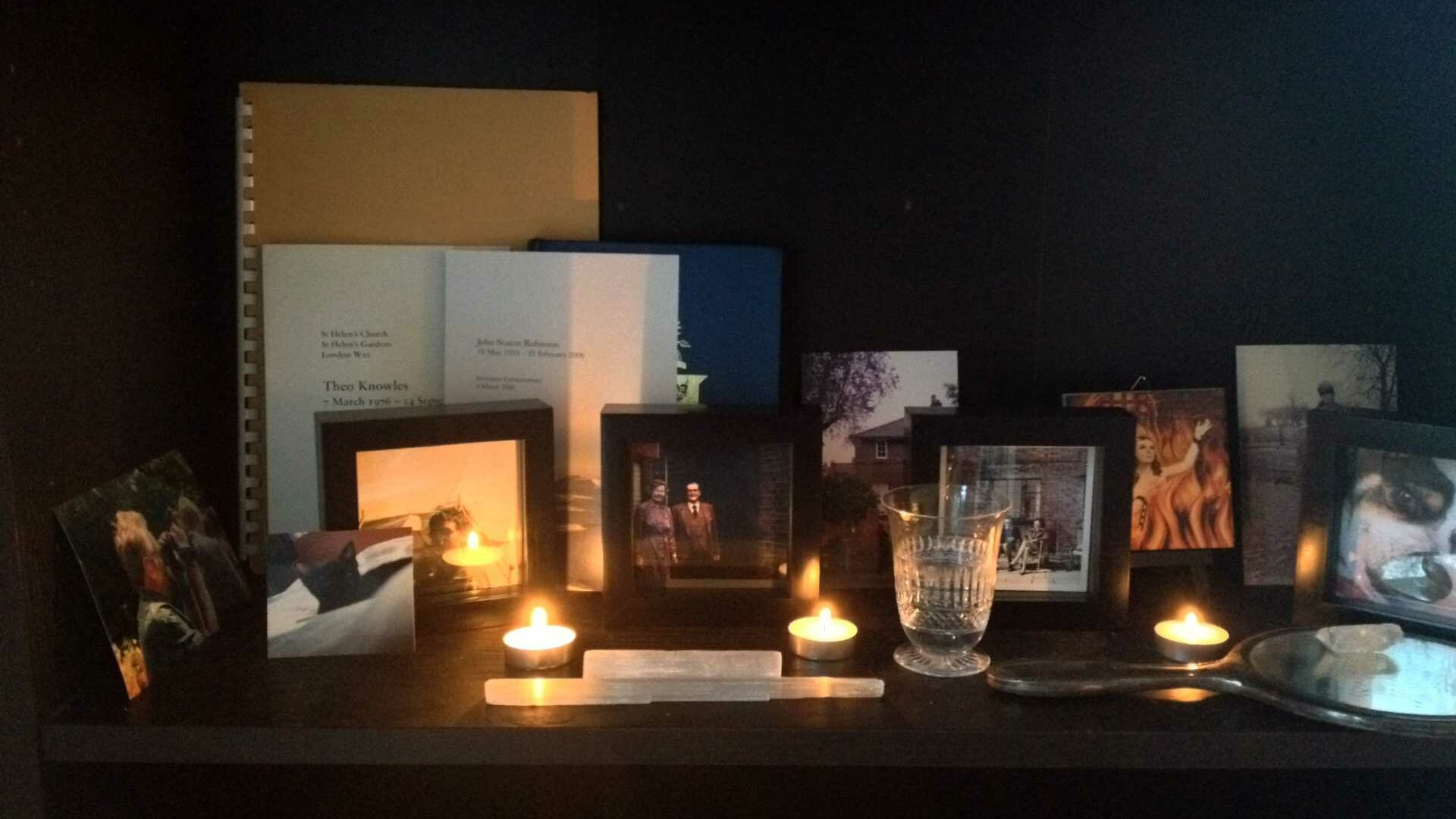 Memento Mori altar - a selection of family images and tea light candles on a dark shelf