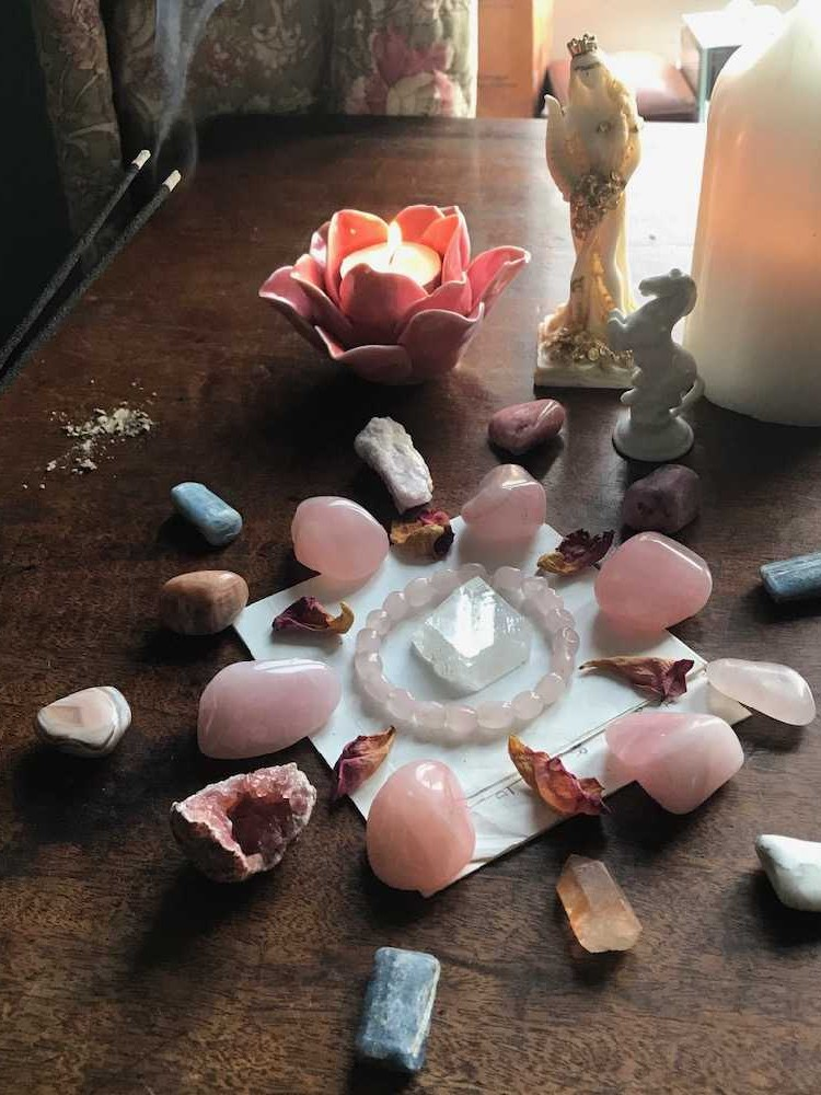 A crystal grid on a wooden altar top, featuring rose quartz, aphophyllite, kyanite, rose petals and more. A figurine of Fortuna stands at the head, and two candles and joss-sticks are burning.