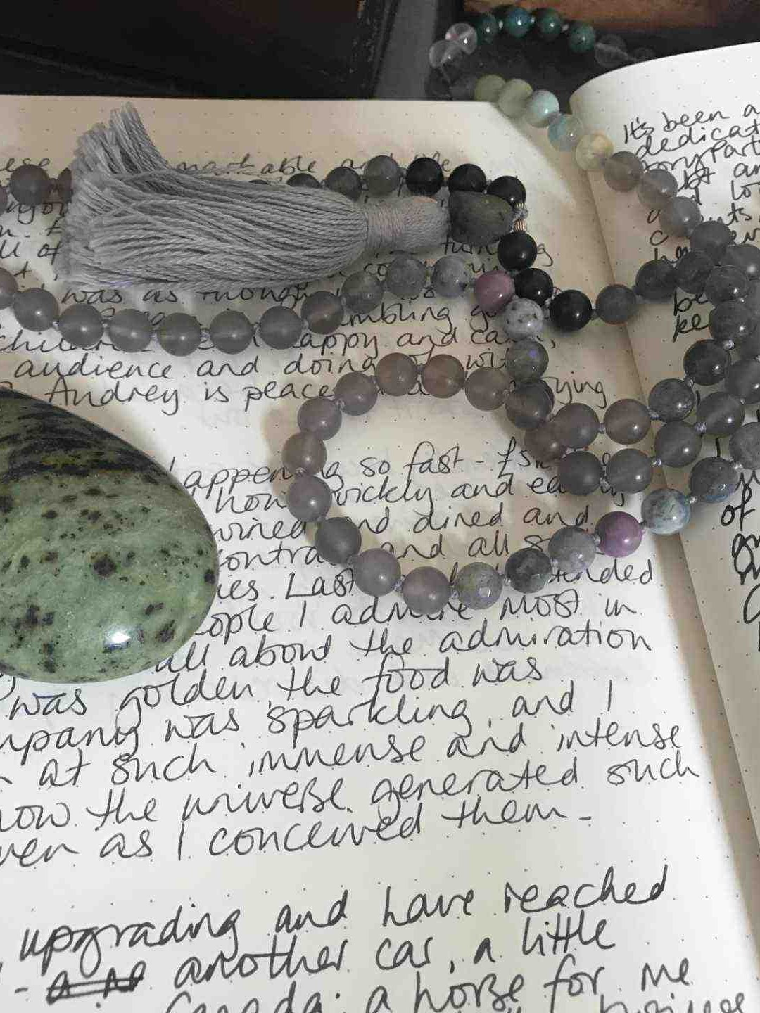 The Fated Forecast Method shown on two journal pages with crystals (quartz, serpentine and a mixed bead mala necklace on top)