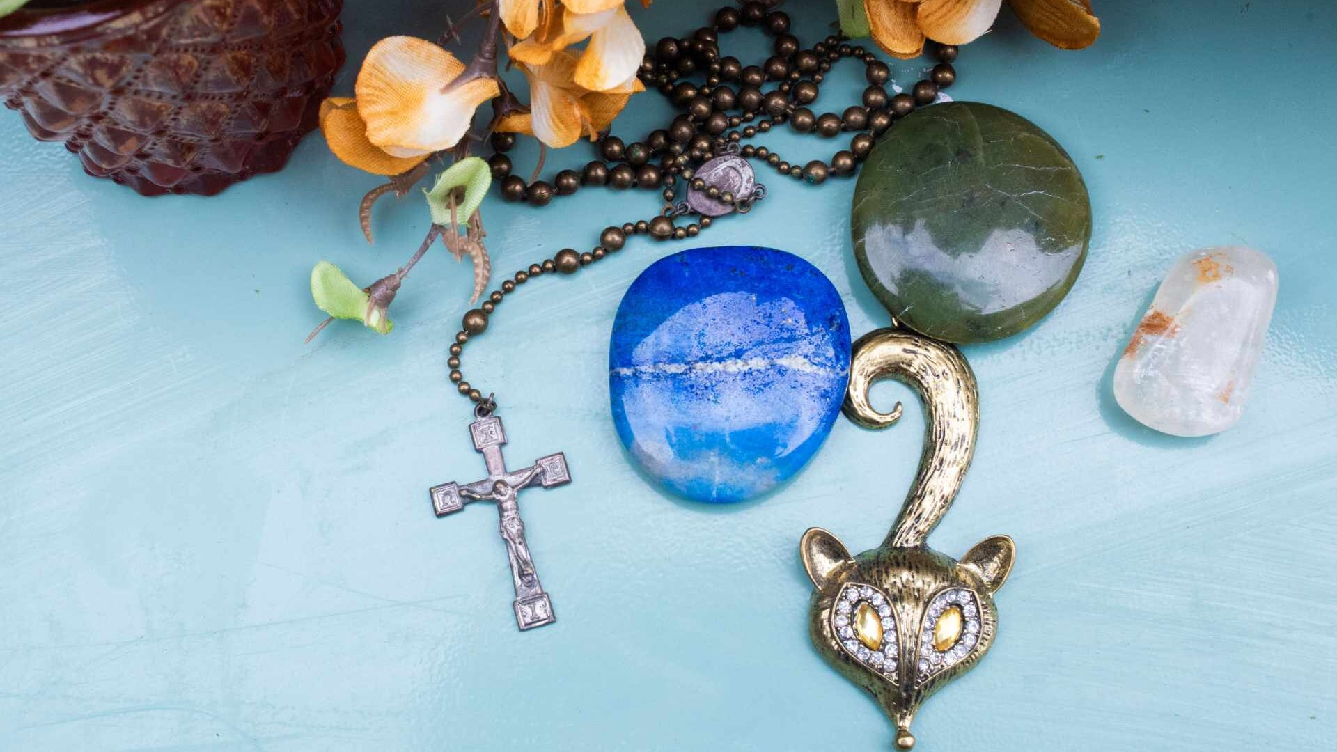 Calling forth magic: a fox talisman, a Christian cross, some orange flowers and a couple of flat, polished crystals rest on a turquoise surface